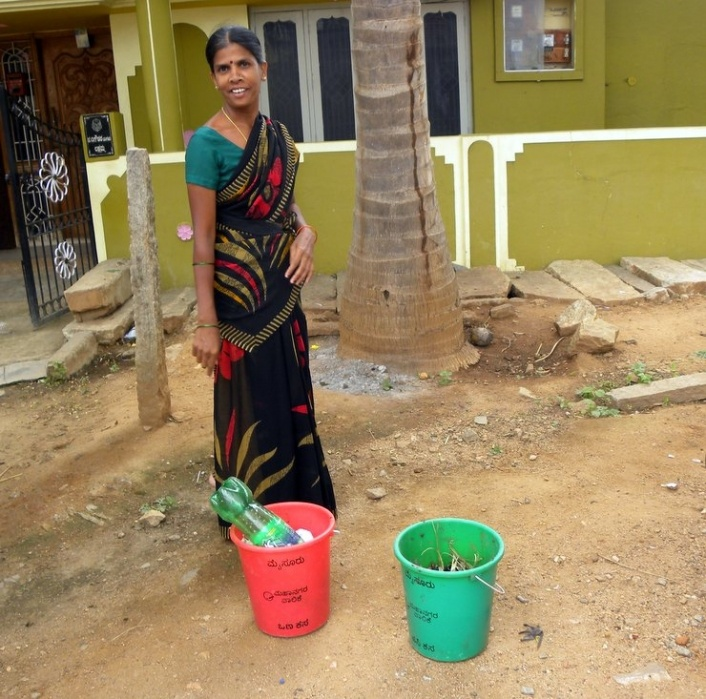 A Mysuru housewife shows off her color-coded trash cans, red for dry waste and green for 'wet' or organic waste. The cans are key to the city's waste-segregation and recycling strategy. (Patralekha Chatterjee)